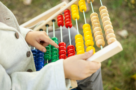 schoolboy: Schoolboy holding abacus. Back to school outdoors