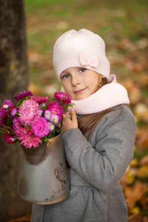 watering pot: Young girl with autumn bouquet in a watering pot, vibrant autumn park background