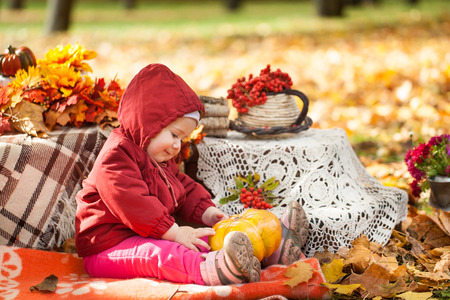 Small girl in autumn park playing with pumpkin, vibrant autumn background