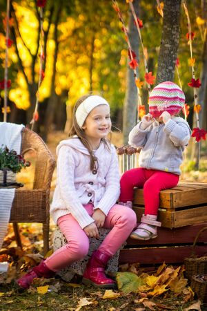 Two sisters sitting on wooden boxes and playing hide-and-seek in the autumn park Stock Photo