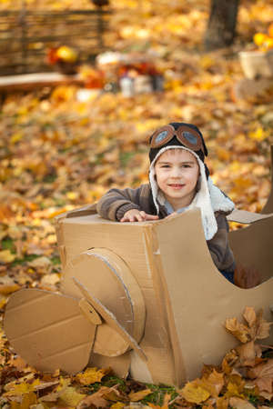 pasteboard: Young boy in autumn park in a pasteboard airplane, vibrant autumn background