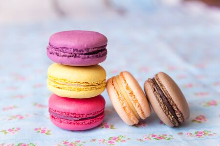 with fillings: Vanilla multicolor french macarons with various fillings on floral napkin