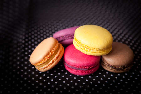 with fillings: Vanilla multicolor french macarons with various fillings on black napkin Stock Photo
