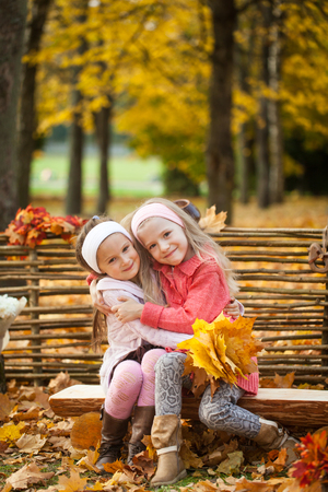 Two girls in autumn park sitting on wooden bench with teddy bear near a fence, vibrant autumn background
