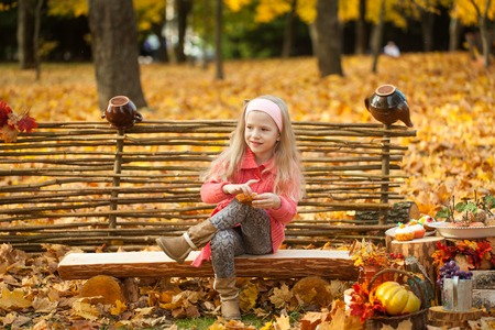 autumn young: Young girl in autumn park on a wooden bench, vibrant autumn background