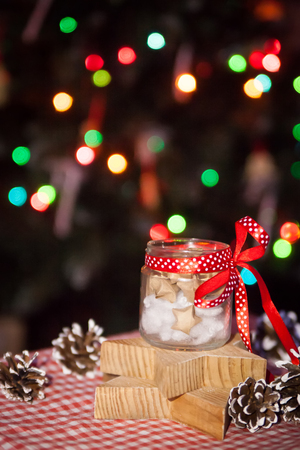 predictions: Glass jar with Christmas predictions on wooden star plates in front of decorated tree and color bokeh Stock Photo