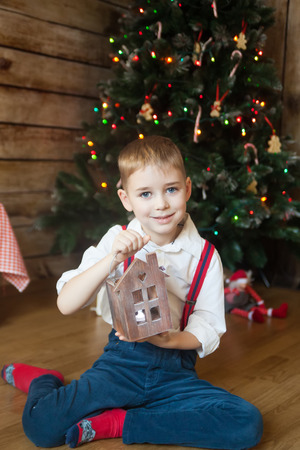 christmastime: Boy with wooden candleholder house sitting in front of decorated Christmas tree