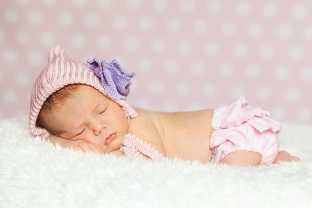 pink panties: Newborn baby girl in a pink bonnet with violet flower and lace panties sleeping on a soft white fur Stock Photo