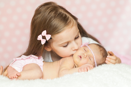 pink panties: Cute little girl kissing her sleeping newborn sister in a pink lace panties and knit headband