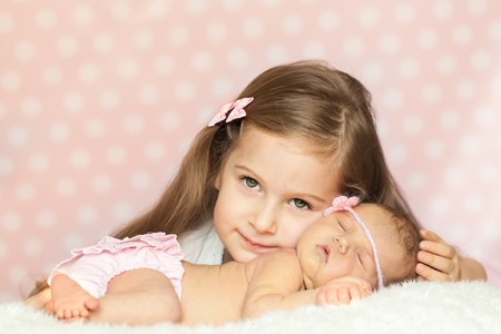 pink panties: Cute little girl with a newborn sister in a pink lace panties and knit headband sleeping on a soft white fur Stock Photo