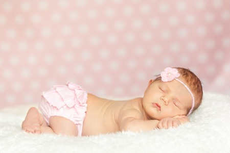 pink panties: Newborn baby girl in a pink lace panties and knit headband sleeping on a soft white fur