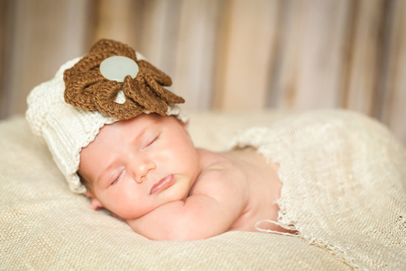 big flower: Newborn baby girl in a knit hat with big flower sleeping on a linen fabric. Natural colors Stock Photo