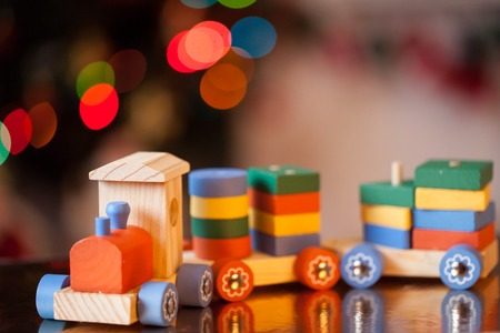Wooden train toy in front of a new year tree lights.