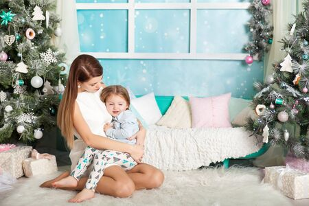 family sofa: Mother and daughter in a Christmas decorated studio in pastel colors Stock Photo
