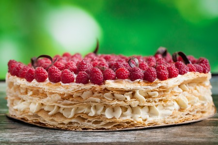 Millefeuille cake with raspberry on wooden background