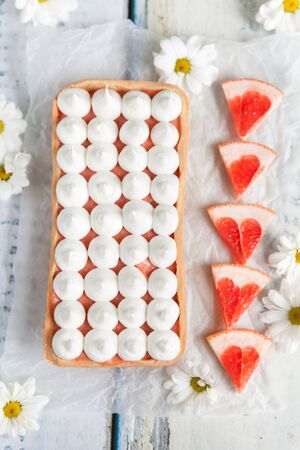 French tart with grapefruit curd and merengue on top with flowers on a backdrop
