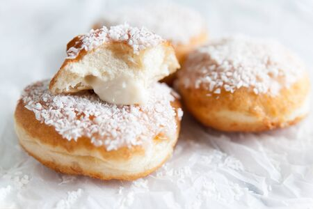 Deep-fried doughnuts filled with coconut custard cream on white baking paper on light background