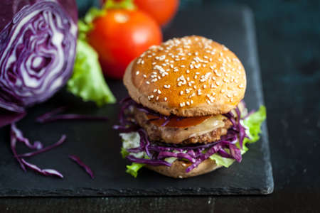 Fresh homemade burger with purple cabbage served over black textured board