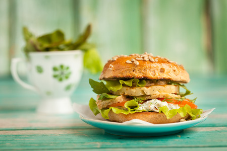 Fresh homemade burger with chicken, grilled pineapple and garlic sauce on on a green background Stock Photo