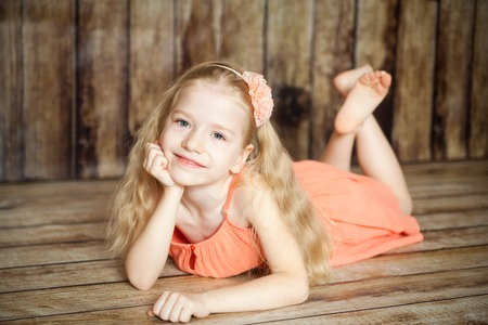 Cute girl dreaming in an easter decorated studio with wooden background