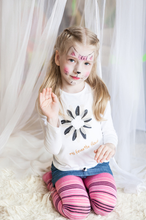Cute little girl with kitty painted face in a light spring studio