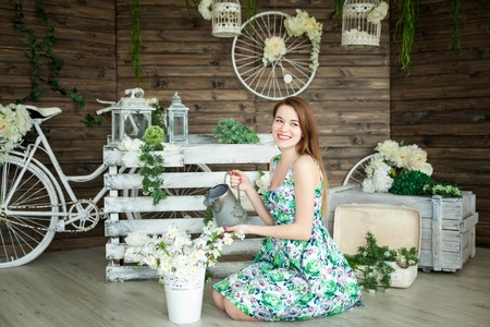 Portrait of a young woman in floral spring summer dress in a spring studio. Rustic decor