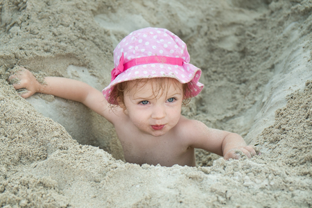 Little blonde girl in a pink panama sitting in a sand hole