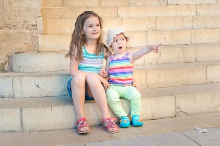 Two girls sitting on outdoor stone stairs. Little suprised girl points with her finger Stock Photo