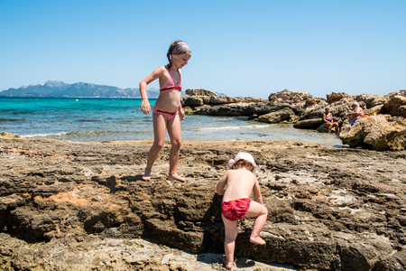 Two sisters playing on stone beach in Mallorca, Spain 스톡 콘텐츠