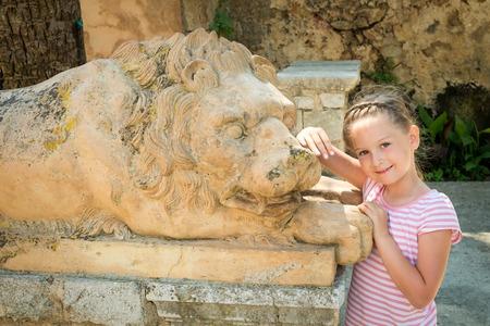 Beautiful cheerful girl with stone lion sculpture. Alfabia gardens in Mallorca 写真素材