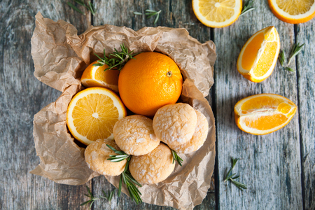 Homemade orange crinkle cookies with powdered sugar icing. Cracked citrus biscuits on wooden background