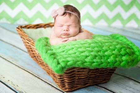 Cute newborn baby girl in a pink knit romper sleeping on a green chunky knit blanket in a basket Stock Photo