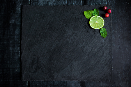 Mojito Cocktail ingredients: cranberries, mint, lime on stone chopping board on wooden dark background. Top View with copy space 写真素材