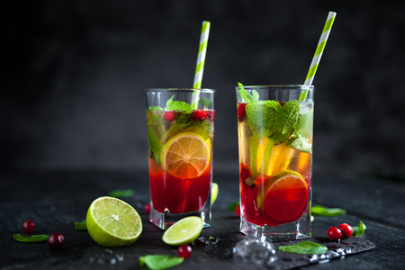 Mojito cocktail with cranberry, lime and mint in highball glass on a grey stone background. Summer alcoholic cocktail