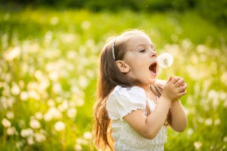 Pequeña niña feliz que sopla la flor del diente de león al aire libre. Fondo borroso en puesta de sol Foto de archivo