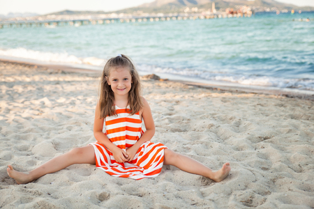 Cute girl in red and white striped dress having fun on a beach on sunset. Mallorca, Spain Stockfoto