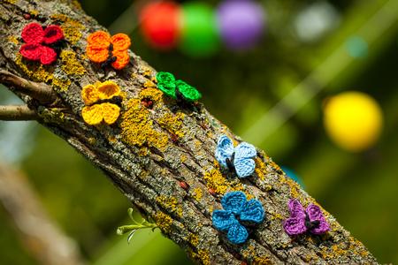 Rainbow crochet butterflies on the tree. Vibrant decor for birthday or wedding summer party