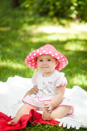 Bright summer berry party in park. Cute little girl in red polca dot panama sitting on the blanket