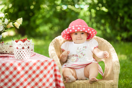 Bright summer berry party in park. Cute girl sitting at a decorated table