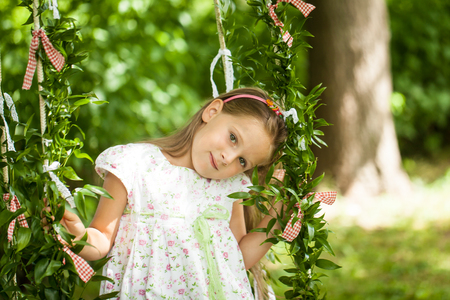 Bright summer berry party in park. Cute girl on the swing