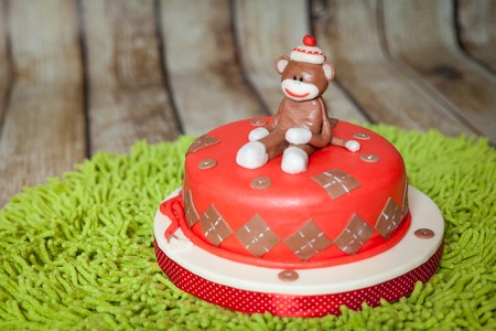 Sock monkey theme birthday cake. Sweet dessert with mastic