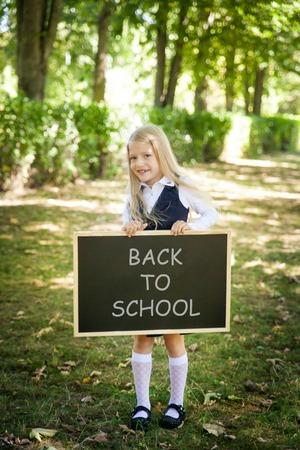 Little school girl in a uniform with a chalkboard. Back to school outdoors
