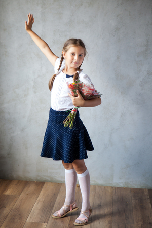 School girl in a uniform with bouquet of autumn flowers. Back to school