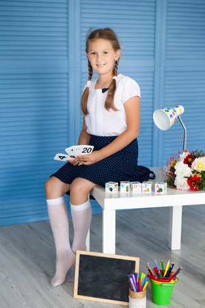 School girl in a uniforn with school subjects on blue background. Back to school. Place for text