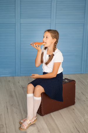 Portrait of a school girl in a uniforn sitting on an old suitcase and eating gingerbread-pencil. Back to school