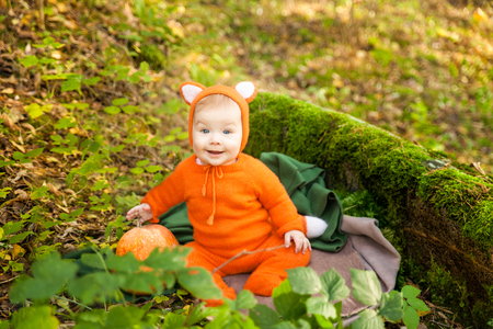 Cute baby girl dressed in fox costume in autumn forest. Fall halloween kids session