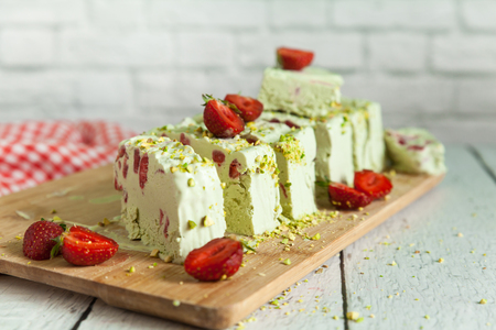 Pistachio ice cream with strawberry and pistachio nuts on a light wooden background
