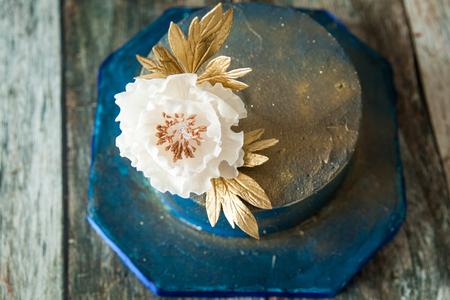 Blue and gold wedding cake with a big sugar flower. 2 Tier blue elegant birthday cake