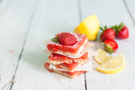 Strawberry lemonade bars for healthy breakfast. Homemade energy slices on white wooden background. Lemon pieces and strawberries