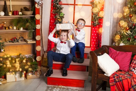 Happy boys holding a present in a warm christmas studio. Cosy gold and red decor
